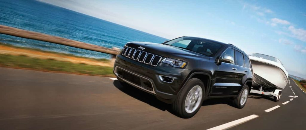 Jeep Grand Cherokee in black driving along a road with a boat trailer attached to the back with an ocean backdrop