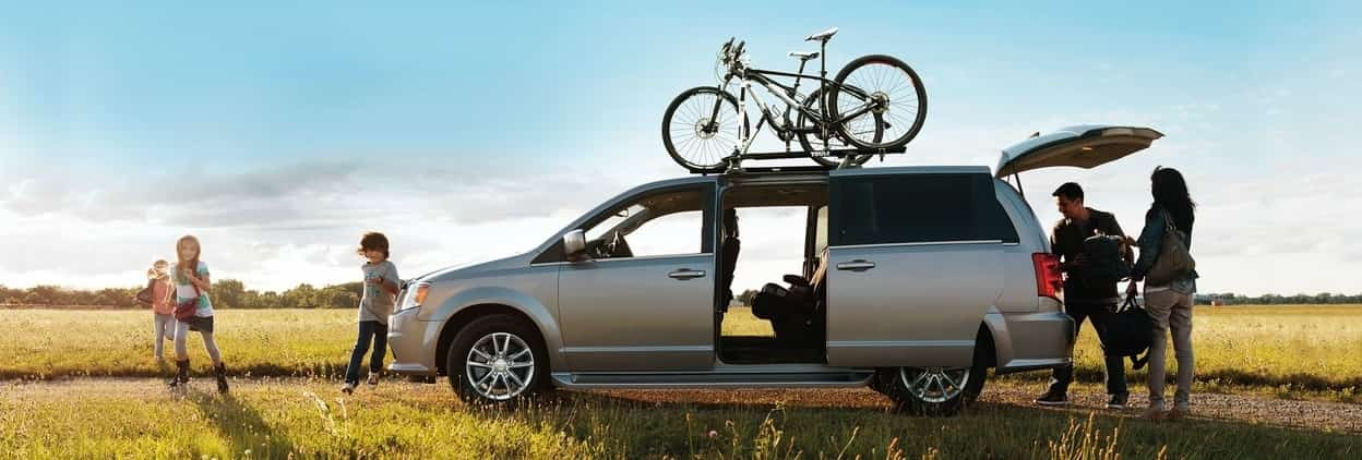 Side profile of the 2019 Dodge Grand Caraven parked in the middle of a field with the sun setting while a bunch of people are loading gear in and out of the van