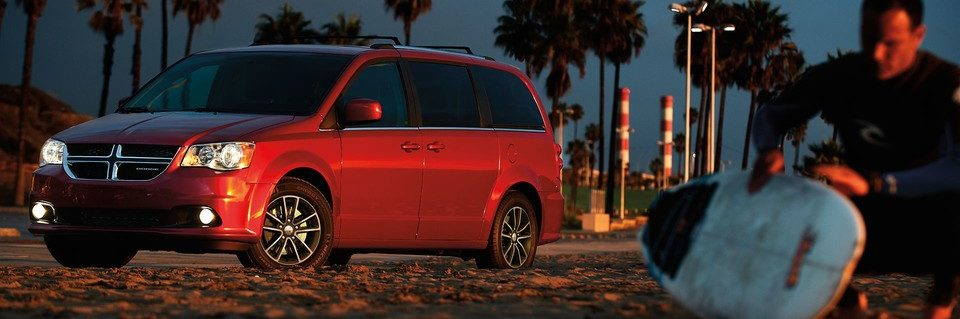 Dodge Grand Caravan shown in red beside surfer on beach