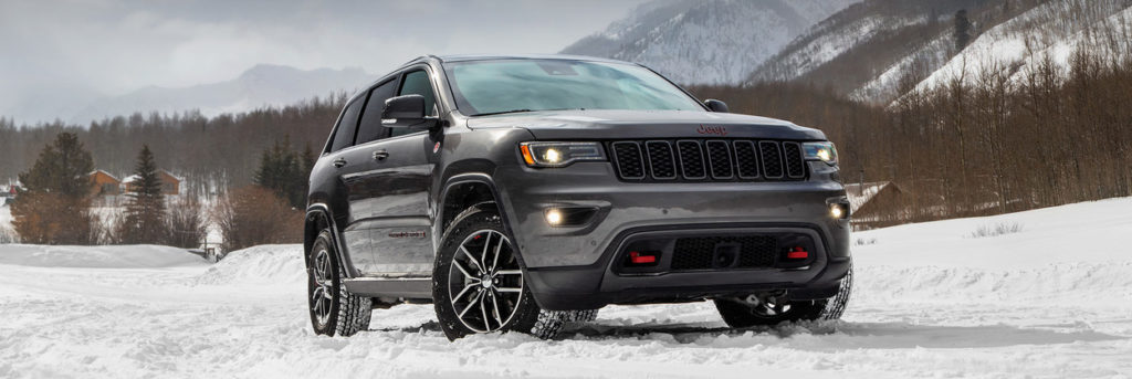 2020 Jeep Grand Cherokee parked in the snow in front of trees and mountains