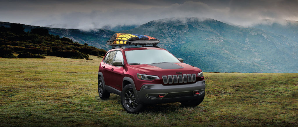 2020 jeep cherokee with camping gear loaded on top, on a mountainside