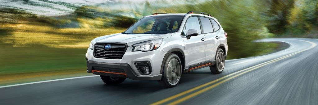 White Subaru Forester driving on highway captured in motion