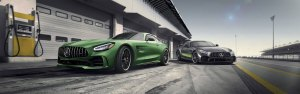 Two AMG GT R Coupes parked in the pit area of a race track