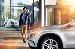 A man walking out of a Mercedes-Benz dealership