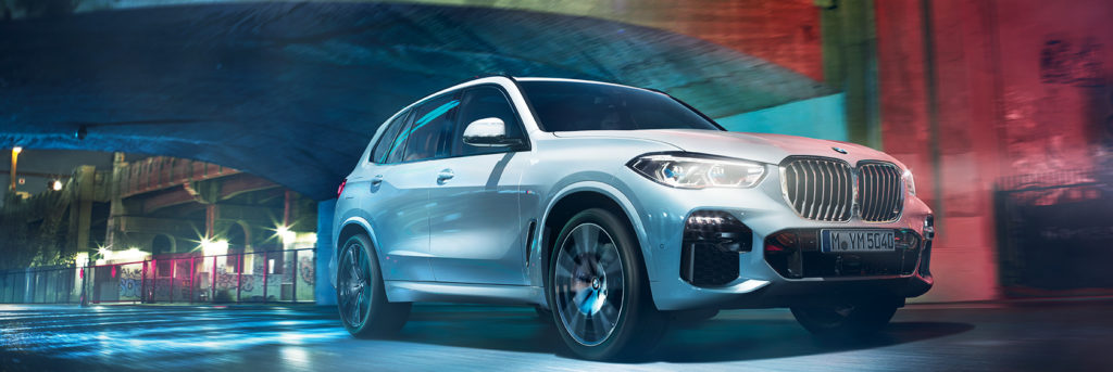 bmw x5 driving under a bridge
