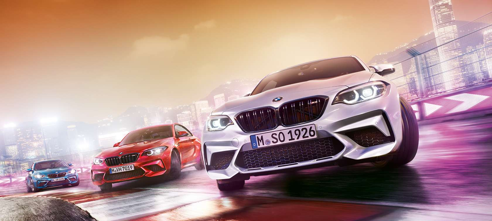 three BMW M2 Competition models drifting along the same curve on a racetrack