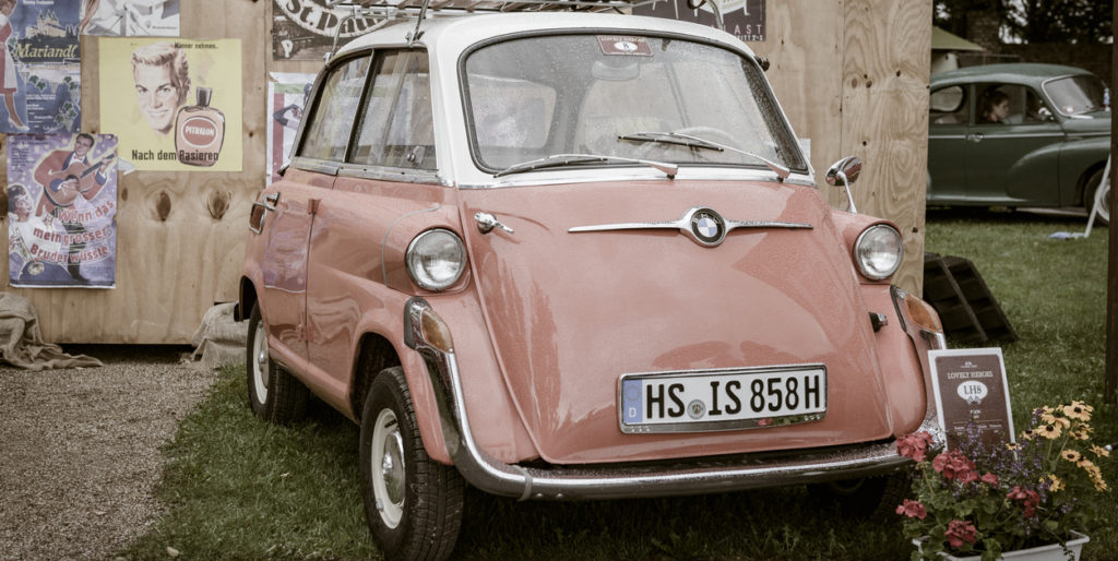 BMW Isetta 600 four-seater 1950s microcar or bubble car. The car is on display during the 2017 Classic Days event at Schloss Dyck. People in the background are looking at the cars.