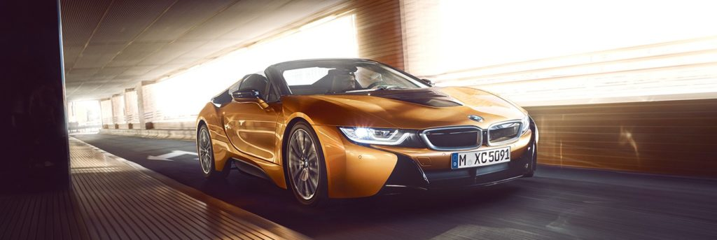 BMW i8 Roadster speeding down a road