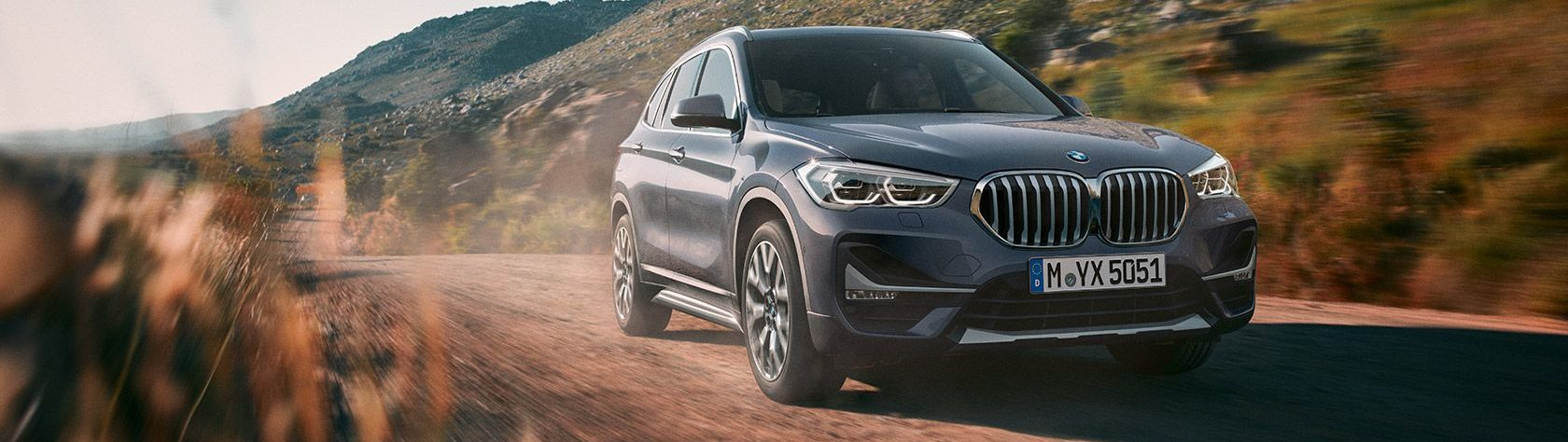 BMW X1 driving down a dusty country road