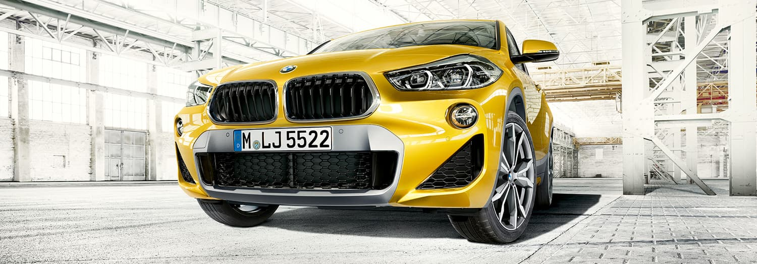 2020 BMW X2 in yellow facing the camera with a low-angled shot of its kidney grille in an empty white warehouse
