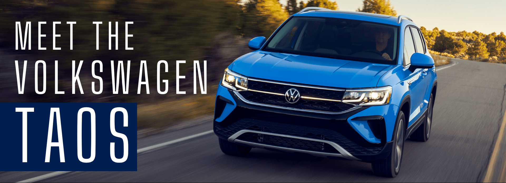 blue 2022 volkswagen taos driving toward the camera down a curved road