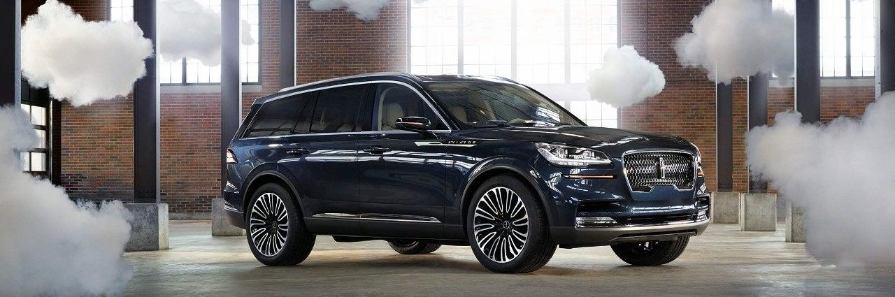 Blue Lincoln Aviator surrounded with prop clouds, stone pillars and brick wall background