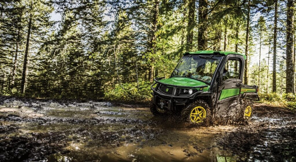 Side exterior view of a Gator machine treading through mud in the forest
