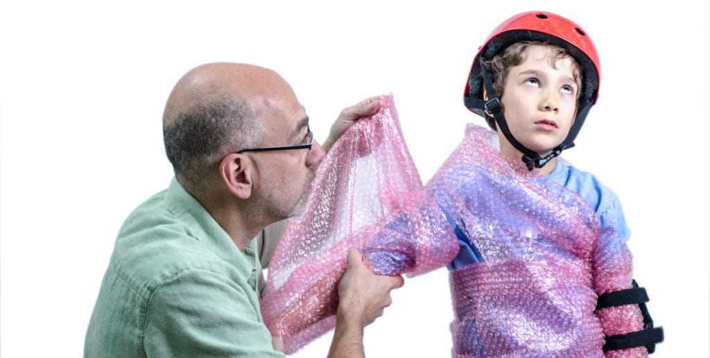 Overprotecting dad putting plastic bubbles over kid before skatebording