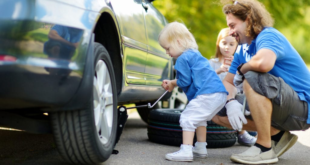 Adorable little girl helping her father to change a car wheel outdoors on beautiful summer day