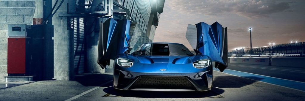 A blue Ford GT, with the gull doors open, parked at night in front of a garage