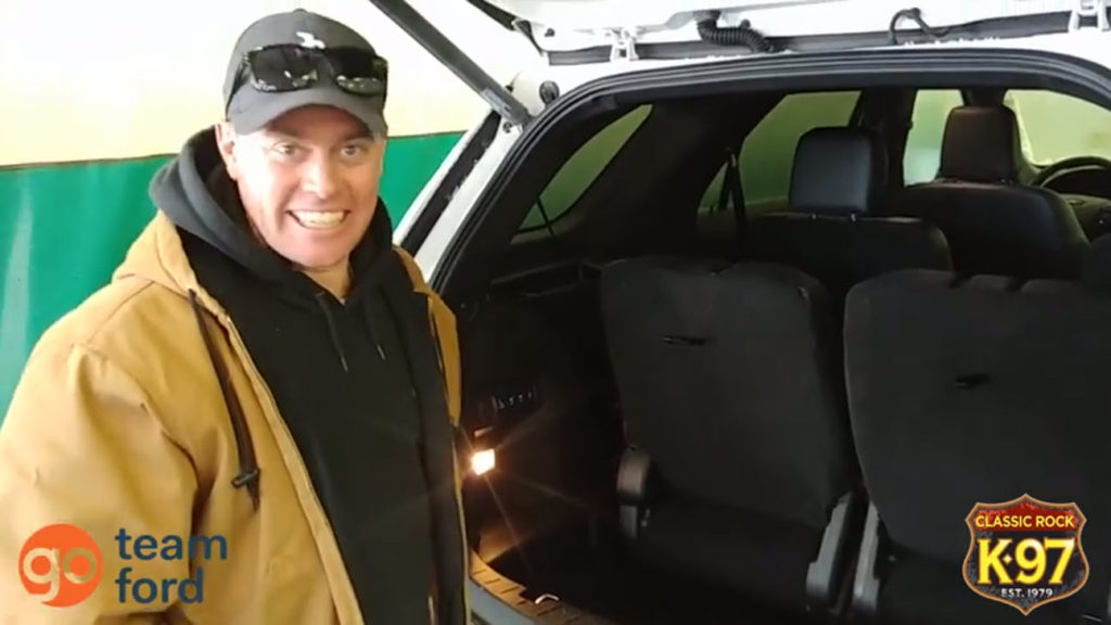 K97's Pete Potipcoe smiles after watching the automatic folding seats in the back of a Ford Explorer fold down