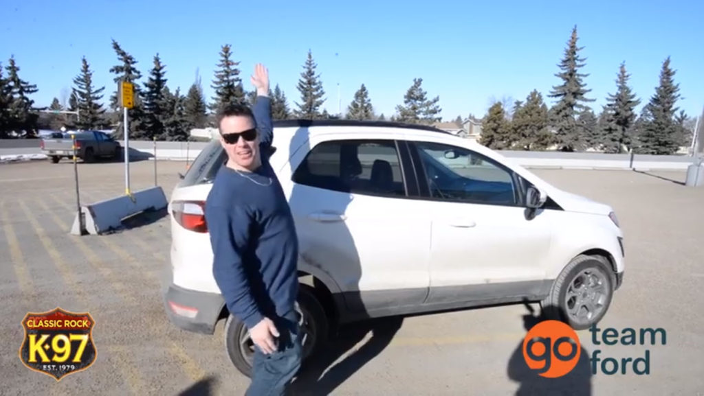 K97's Pete Potipcoe poses next to a white 2019 Ford EcoSport SE in a parking lot on a sunny day
