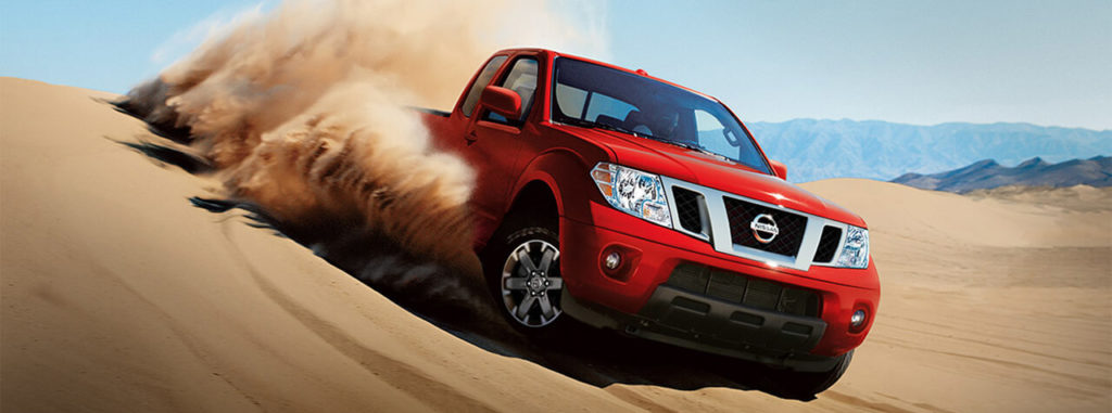 the 2019 nissan frontier in red, driving in a desert