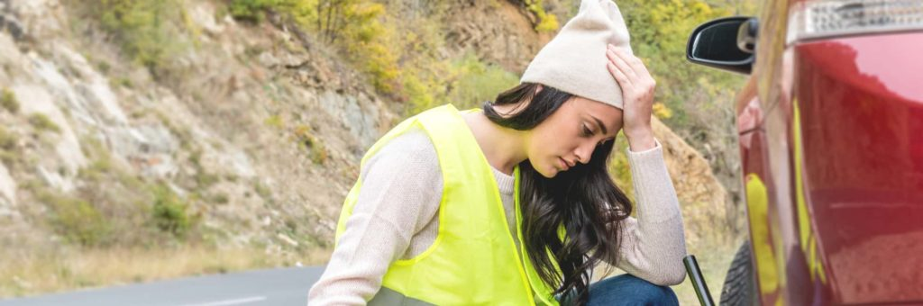 A young woman in a yellow reflective vest is frustrated over having to change a flat tire