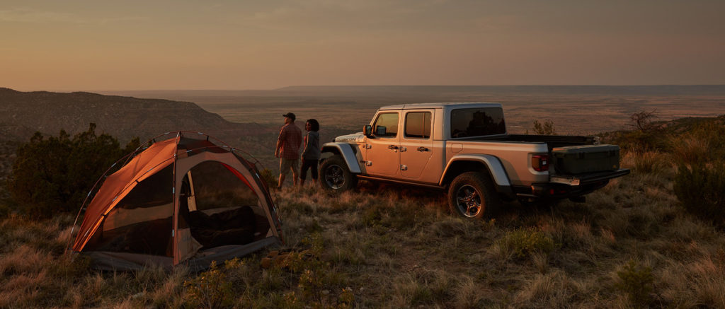 A couple stands looking over the horizon next to a tent, and their 2020 Jeep Gladiator