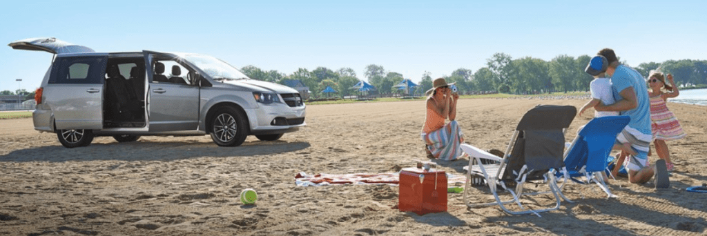 Dodge Grand Caravan parked on the beach with a family having a picnic.