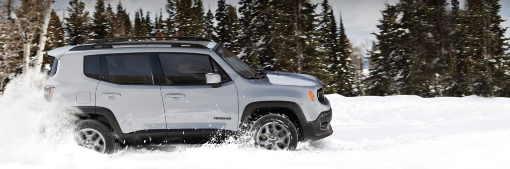 Side profile of a Jeep Rengade driving in the snow