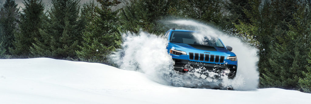 2019 Jeep Cherokee driving through a cloud of snow on a snow covered hill