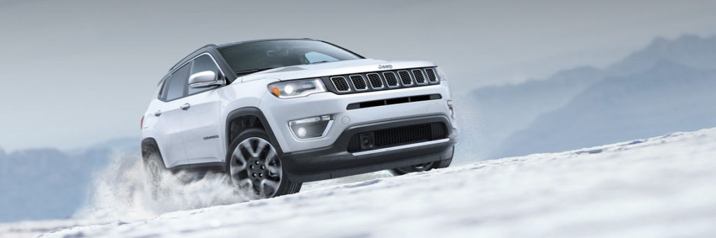 White Jeep Compass driving through snow