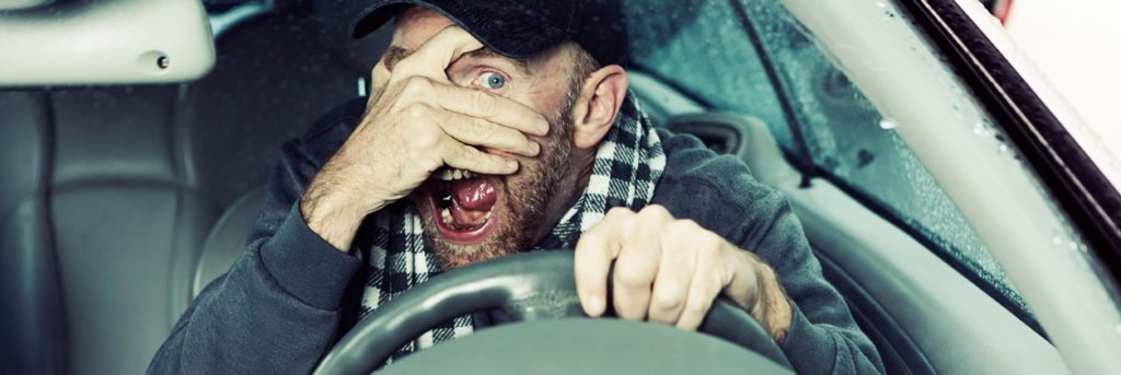 This mature male driver looks terrified, hands nearly covering his eyes and mouth wide open. Looks like an accident has happened, or is about to! Shot through the car's windscreen.