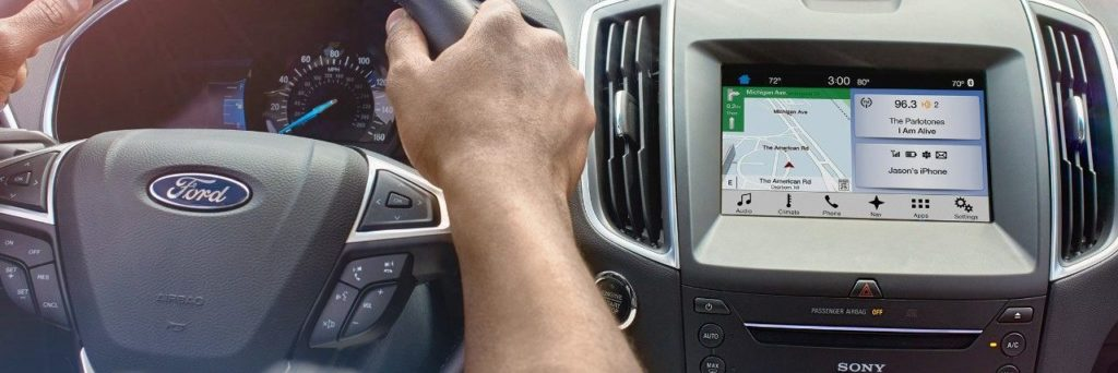 Ford SYNC system displayed on touschreen dashboard next to a Ford branded steering wheel