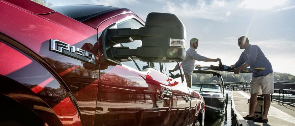 Side shot of Red F-150 towing a motor boat