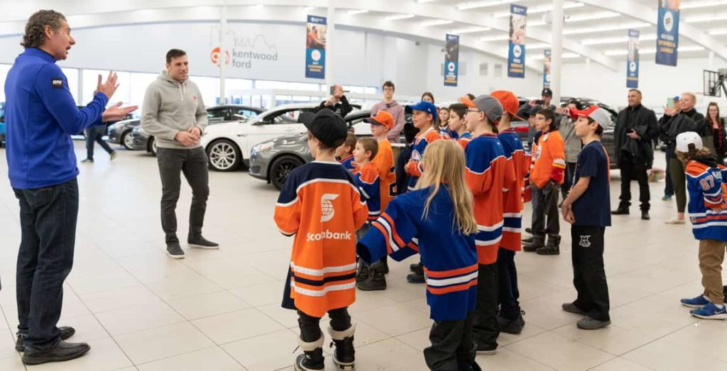 Milan Lucic and Gene Principe greeting the Atom Millwoods Bruins minor league hockey team at Kentwood Ford's Used Car Supercenter