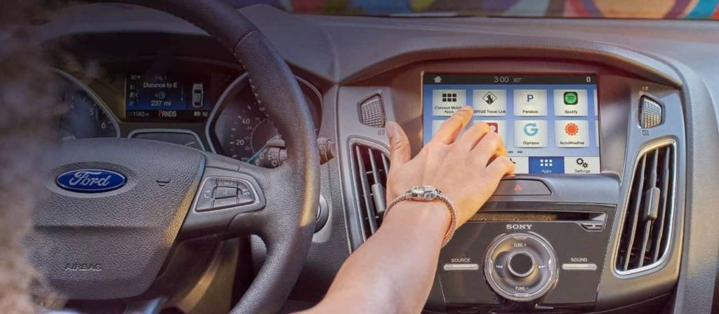 Hand reaching out to the touchscreen of the Ford SYNC infotainment system