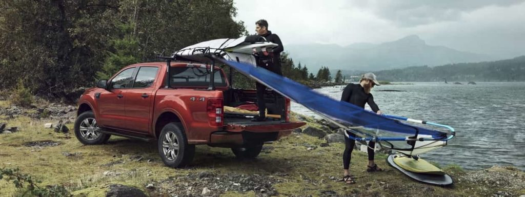 2019 Ford Ranger in oragne with two people loading a kayak on top of the rack