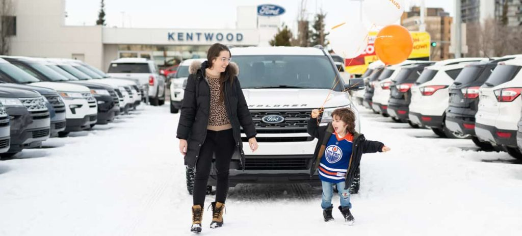 Kira Paran and her son standing in front of a white Ford Explorer with the car dealership parking lot in the background