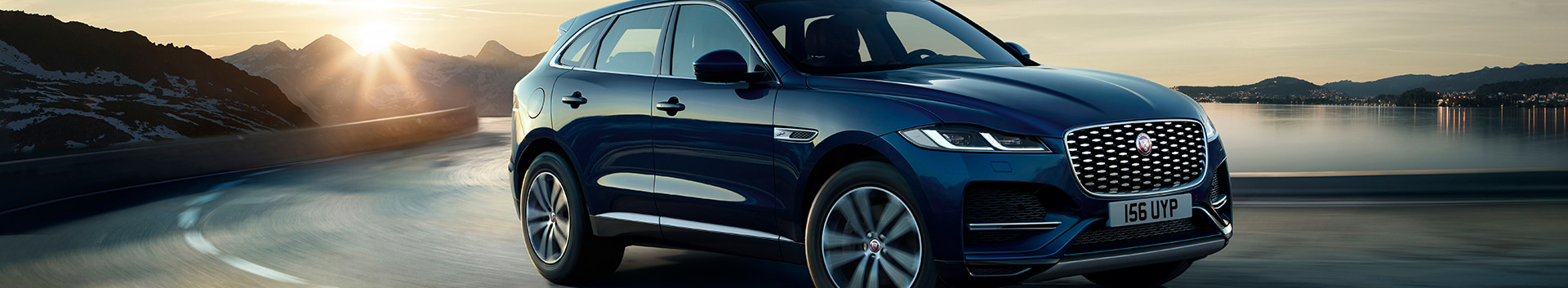 Front 3/4 exterior view of the 2021 Jaguar F-Pace driving across the highway