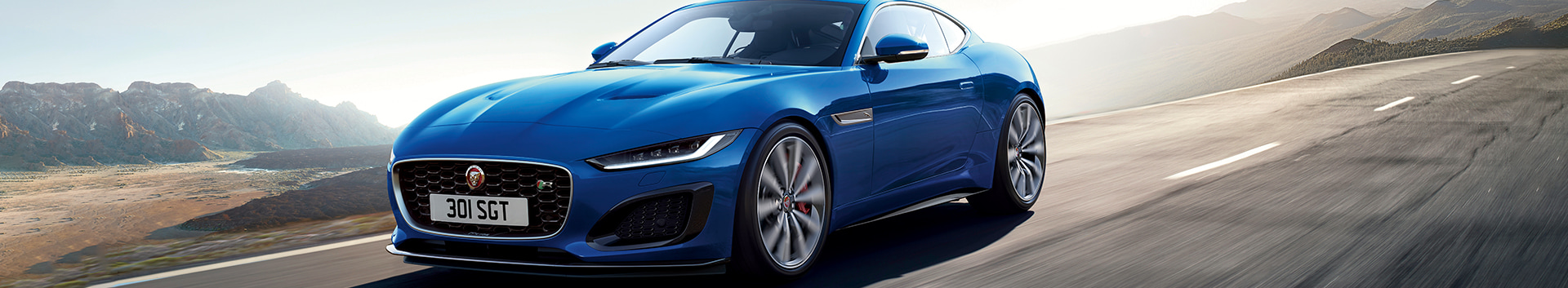 Front 3/4 exterior view of the Jaguar 2021 F-Type driving through the highway