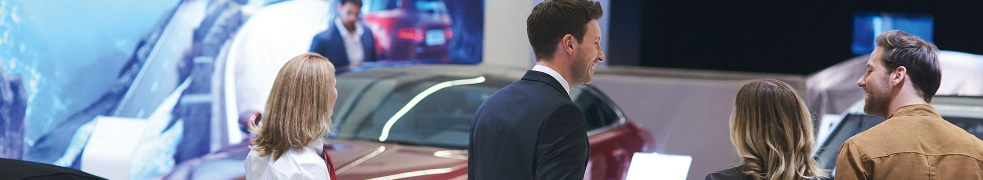 Jaguar staff greeting and showing their customers around the dealership in the showroom