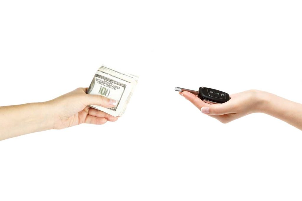 Female hands hold car keys and stack of dollars on white background