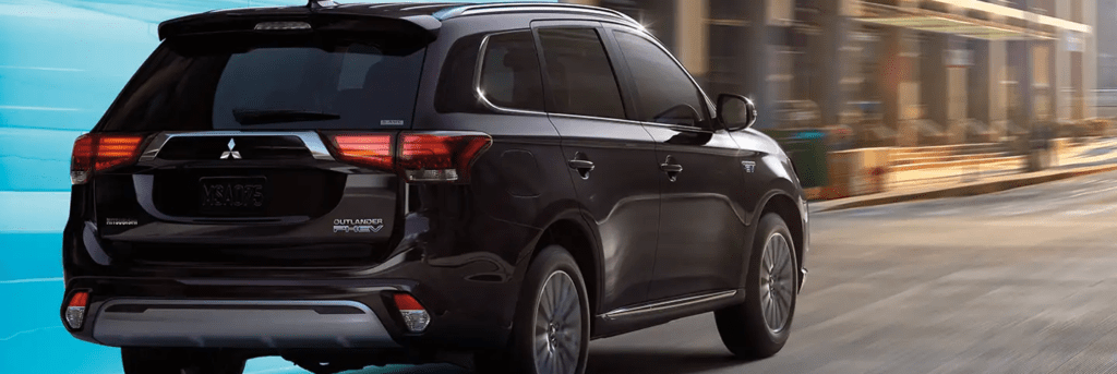 Rear of the Outlander PHEV driving through a two-paneled graphic