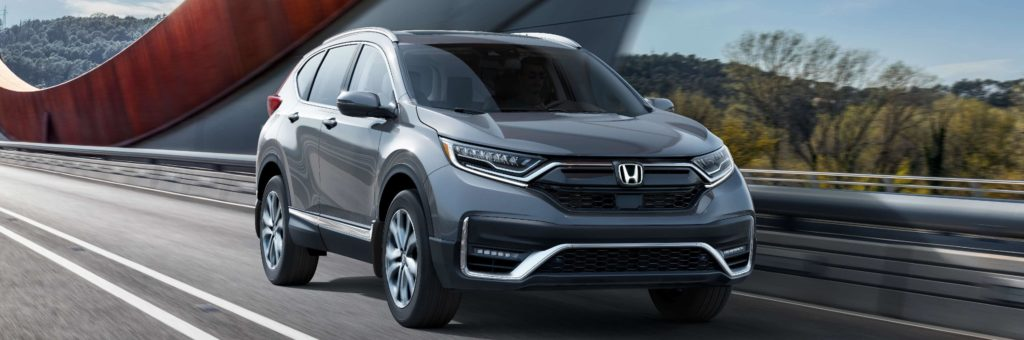 The 2020 Honda CR-V shown in silver driving across bridge
