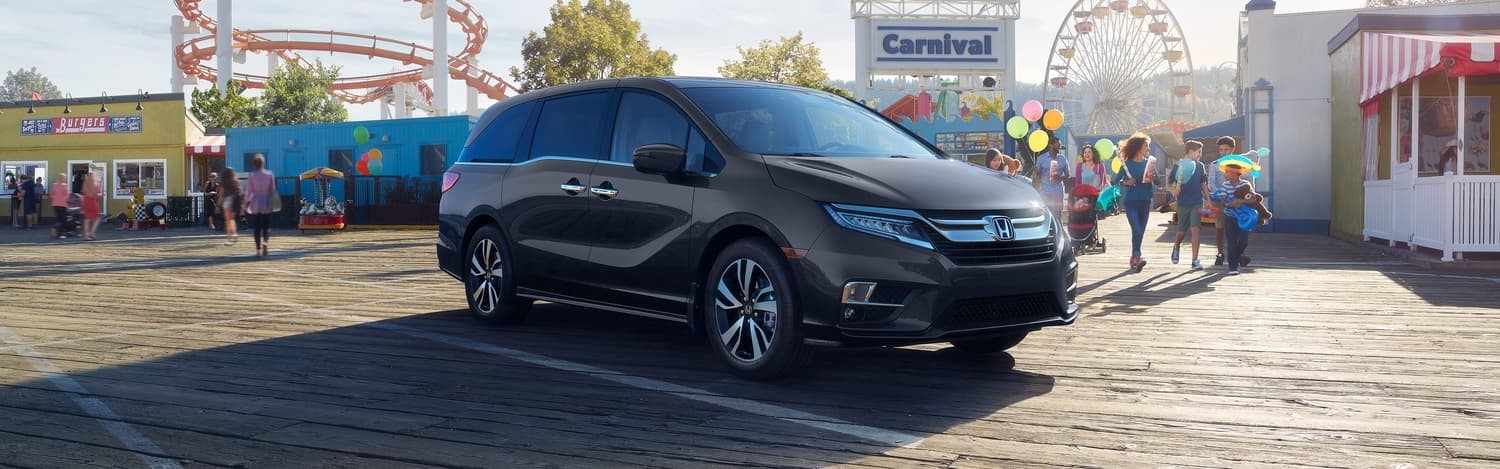 2020 Honda Odyssey in Black parked in front of a carnival