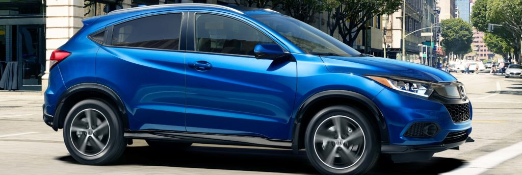Profile shot of 2020 Honda HR-V shown in blue in city intersection in daytime