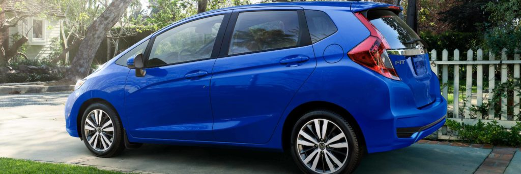 Side of Honda Fit parked in a driveway