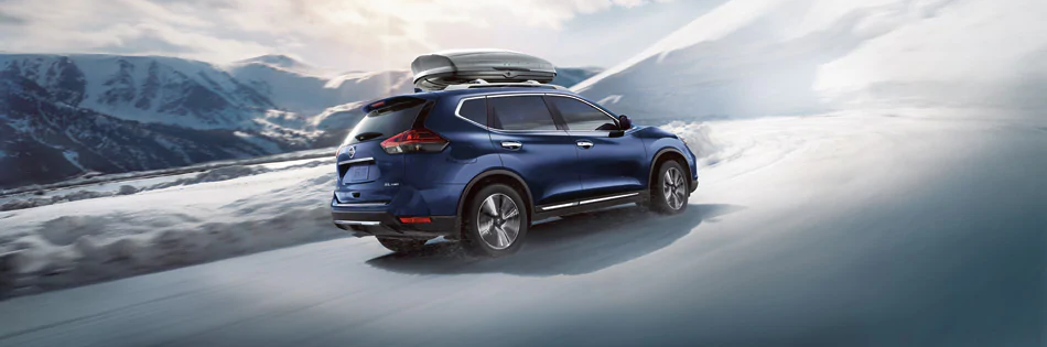 2020 Nissan Rogue shown in blue driving on winter road