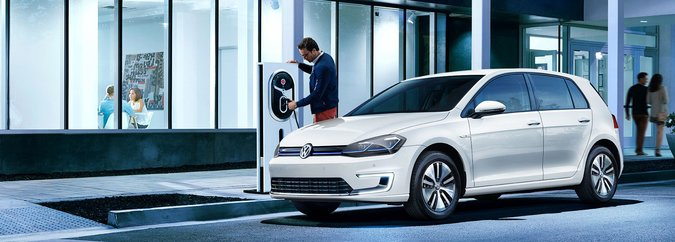 Front 3/4 exterior view of the 2020 e-Golf parked on the side of the street next to a charging station