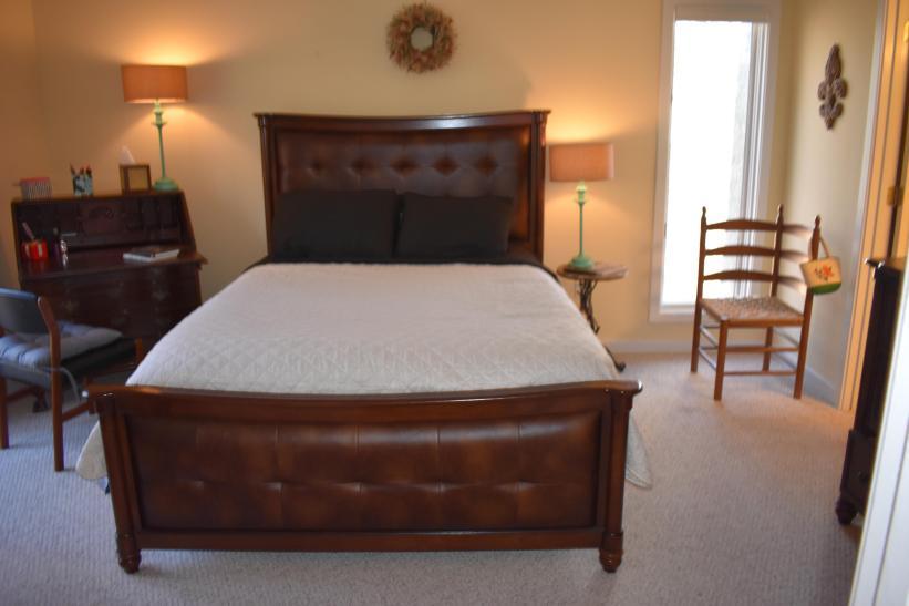 Main Floor Queen Bedroom With Full Private Bath, Closet, dresser, TV, Desk Chair, Floor to Ceiling Windows