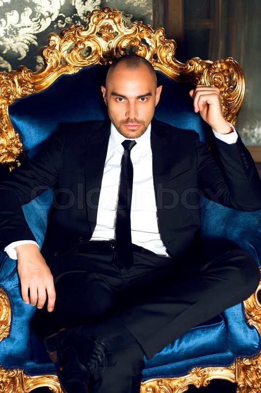 Handsome young muscular man wearing stylish black suit