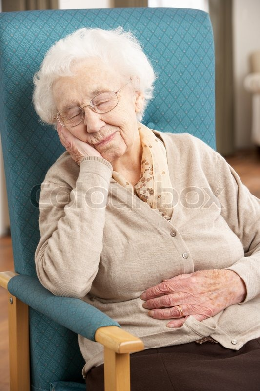 Senior Woman Resting In Chair At Home  Stock Photo